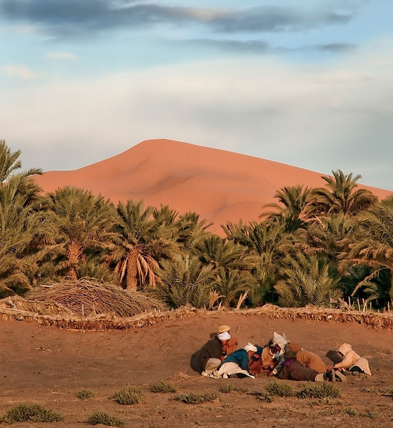 Local men playing games on the desert sand.