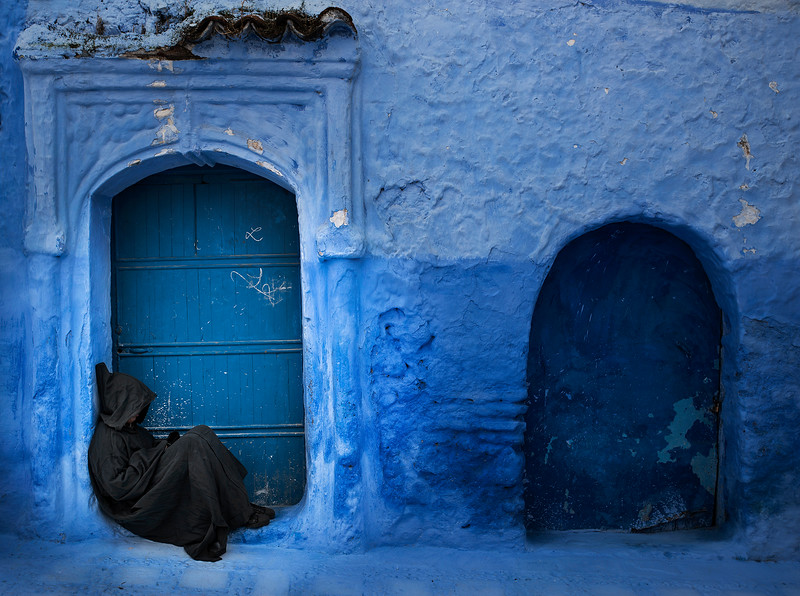 A man sits outside his home in the blue town of Chefchaouen.<br /> Chefchaouen's blue walls are a popular subject of interest. There are several theories as to why the walls were painted blue. One popular theory is that the blue keeps mosquitos away, another is that Jews introduced the blue when they took refuge from Hitler in the 1930s. The blue is said to symbolize the sky and heaven, and serve as a reminder to lead a spiritual life.<br /> <br /> Chefchaouen, Morocco, 2018.