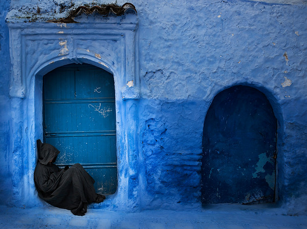A man sits outside his home in the blue town of Chefchaouen. Chefchaouen's blue walls are a popular subject of interest. There are several theories as to why the walls were painted blue. One popular theory is that the blue keeps mosquitos away, another is that Jews introduced the blue when they took refuge from Hitler in the 1930s. The blue is said to symbolize the sky and heaven, and serve as a reminder to lead a spiritual life.  Chefchaouen, Morocco, 2018.