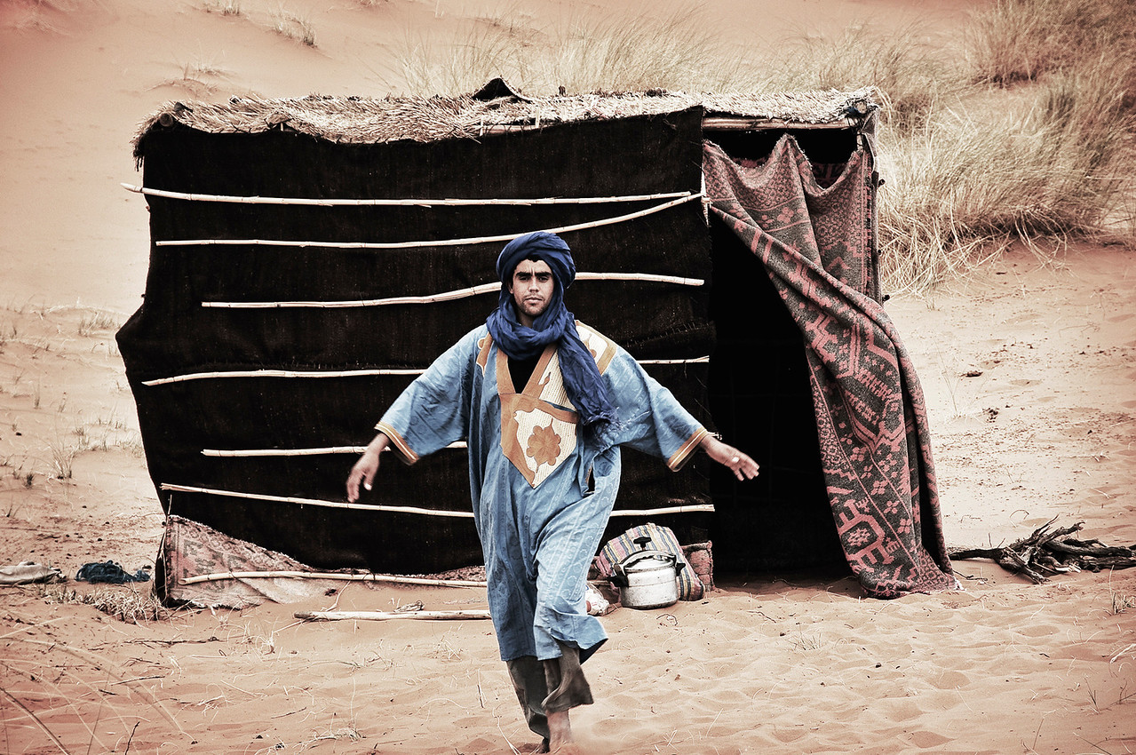 Beduin man coming out of his tent. the blue kaftan and turban is what gives them the nick name, blue men.<br /> <br /> Erg chebbi, Morocco, 2010.