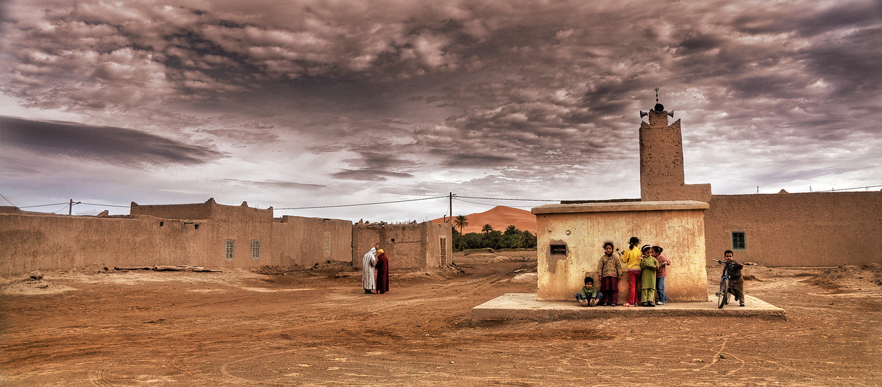Kids play by the local mosque, with the desert sand dunes in the background. <br /> <br /> Hassi Labied, Morocco, 2009.
