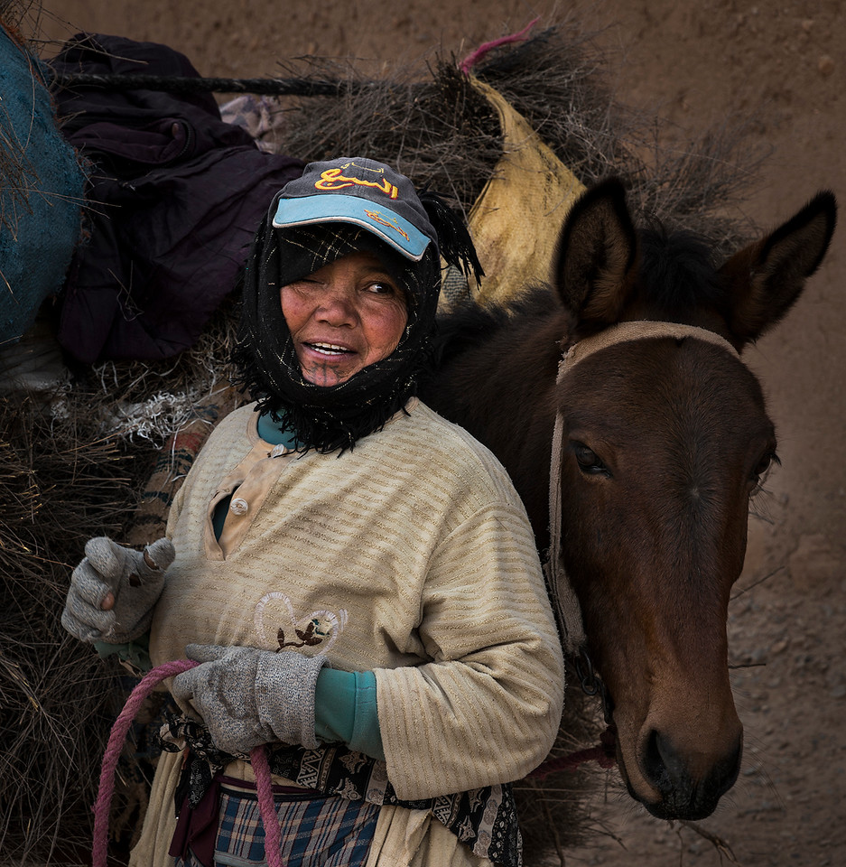 Berber woman and her donkey in the high Atlas mountains.<br /> <br /> Tamtetoucht, Morocco, 2018