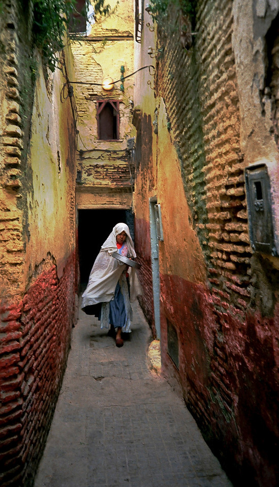 Woman walking through a small street in the Medina.<br /> <br /> Souk El Arba, Morocco, 1995.
