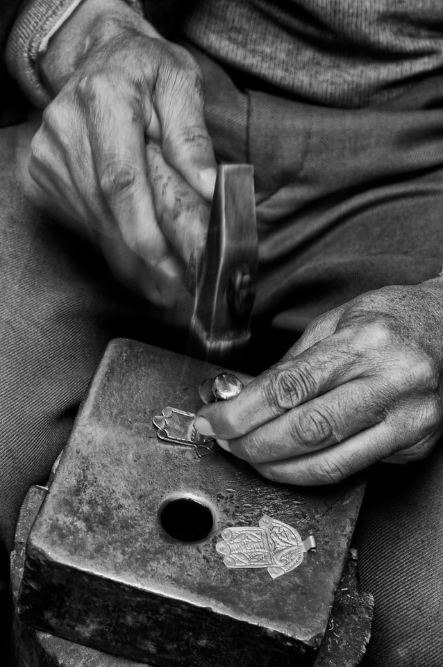 Metal worker making the popular hand of Fatima, said to help against the evil eye.<br /> <br /> Marrakesh, Morocco, 2010.