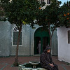 man sits outside a mosque in the blue town of Chefchaouen.<br /> <br /> Morocco, 2018