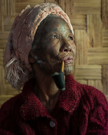 Portrait of a woman from the Muun tribe with her traditional face tattoo. Many tribal women from the Chin State smoke tobacco regularly from a traditional pipe. It is said that this practice began as a way to repel insects whilst working in the countryside.  Chin State, Myanmar.