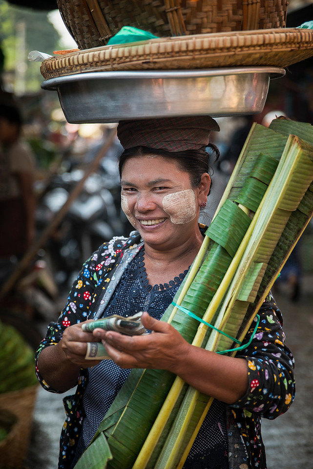 A street vendor counting her earnings at the food market in Mandalay.<br /> <br /> Myanmar 2017