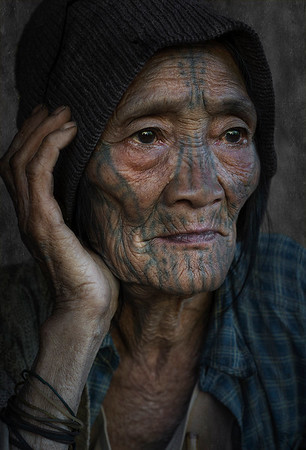 An old lady from the Muun tribe as evidenced by the design of the tattoo on her face.  Chin State, Myanmar, 2017