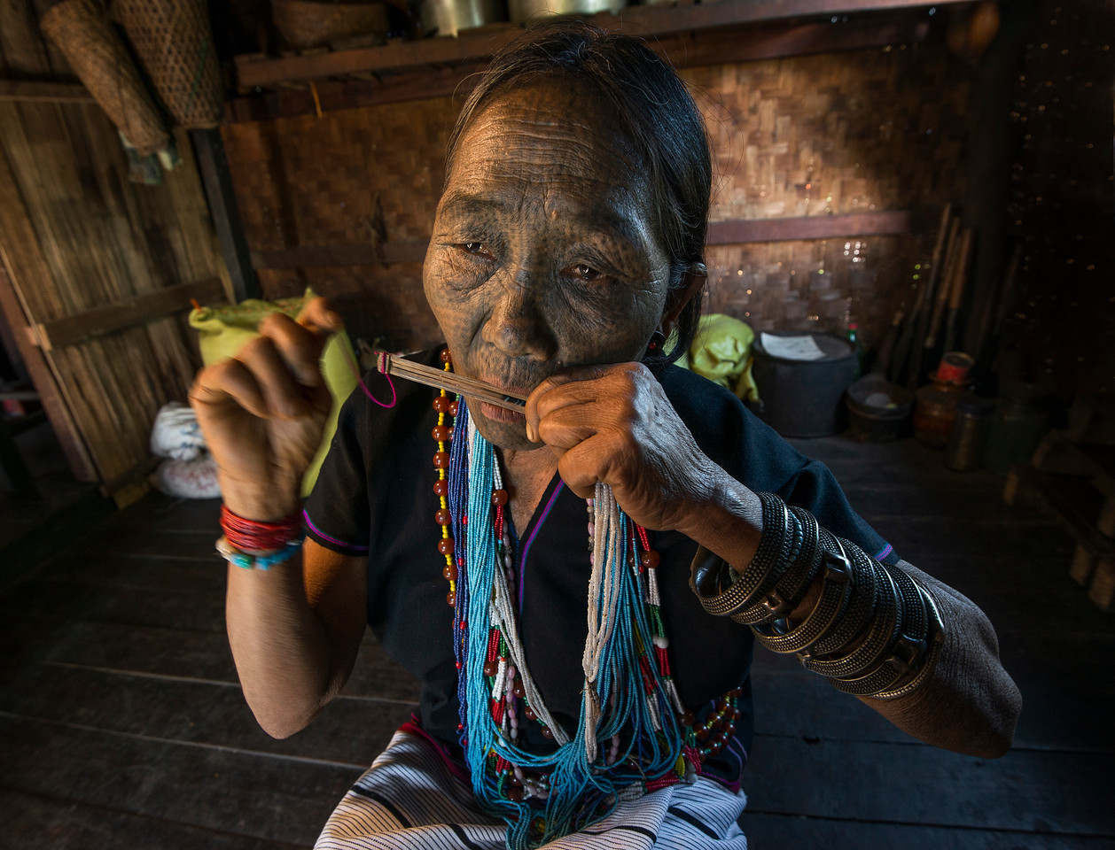 This is Pwe Htang a 70 year old lady from the Daai Tribe. She lives in a small hamlet outside Kampetlet. Pwe learned to play the nose flute and a small, harp type instrument at the age of 14.  She learned to play by watching others in the village. At the young age of 15 she decided to have her face tattooed. She recalls how there was a lot of pressure put on her by others in the village. They explained that she would not be able to find a husband without the tattoos. She did marry eventually but her husband died recently and she now lives with her only son. <br /> <br /> Chin State, Myanmar, 2017