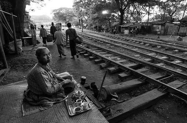 An elderly lady sits outside her tiny wooden home beside the rail tracks and waits for the afternoon train to go past.  Maiktila, Myanmar,2017.