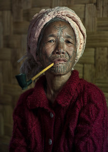 A woman from the Muun tribe smoking her traditional pipe. Most of the tribal women in this part of Myanmar begin to smoke at a very early age as a way to keep insects away when working in the fields.   Chin State, Myanmar, 2017