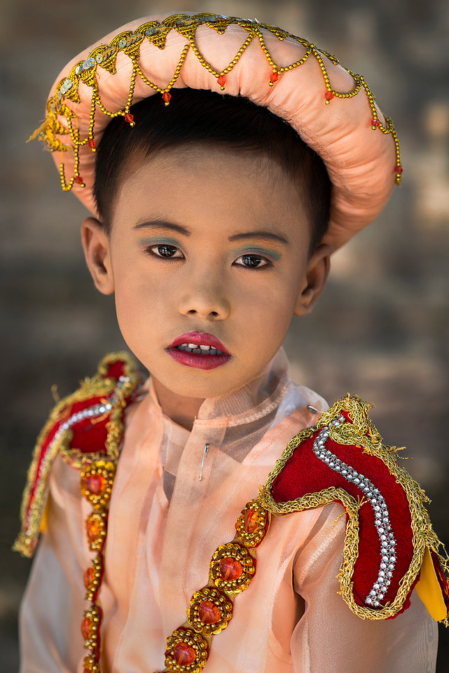 "For a boy in Myanmar it is customary to enter a monastery between the age 10 and 20 as a Buddhist novice for at least one week. Sometimes the boys are even younger, and in rare cases they are only 5 or 6 years old. For Burmese people, the novice hood initiation is a very important ceremony and a big event as a family. The novitiation ceremony is called ""Shinbyu"" in Burmese language. Shinbyu ceremonies are held throughout the whole country, in villages as well as in big cities. Often families send their sons at the same time to the monastery and celebrate the Shinbyu ceremony together. Celebrating together saves costs, because the event with music and traditional dresses is expensive. But it is also a wonderful opportunity for the families to organize a procession through the village as a kind of village festival."