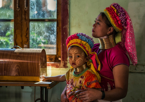A Young mother from the Kayan tribe with her little daughter. Both of them wearing the traditional rings around the neck.  Kayah State, Myanmar, 2017