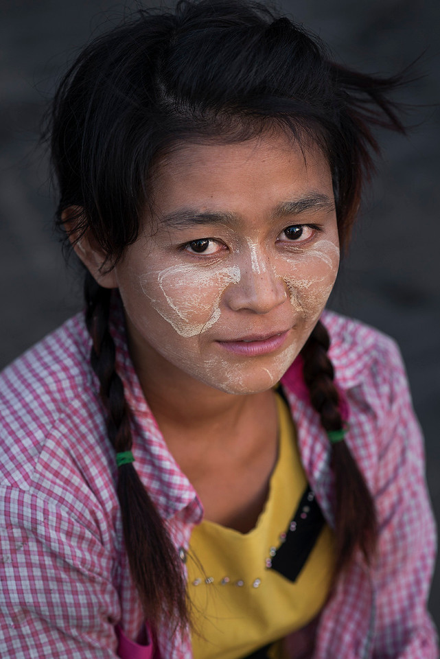 Portrait of a young girl with thanaka on her face.<br /> <br /> Mandalay, Myanmar 2017