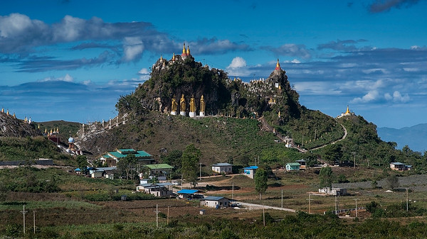 A group of golden Buddhas adorne a rocky landscape.   Myanmar.