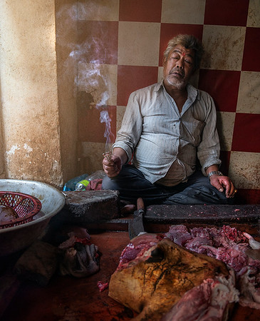 A butcher holding an incense  stick whilst praying for a productive day.   Bhaktapur, Nepal, 2019