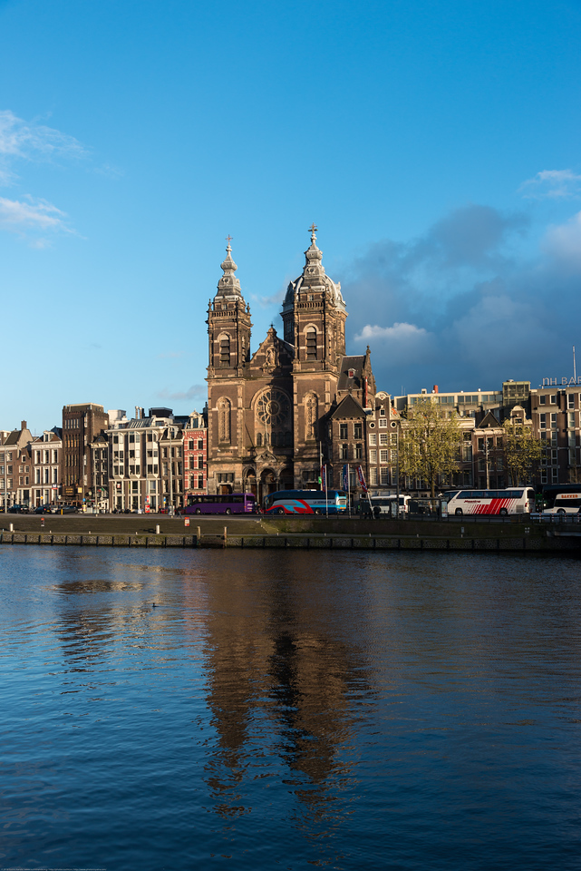 "Church of Saint Nicholas, Prins Hendrikkade 73, 1012 AD Amsterdam, Netherlands seen across the Amstel river which runs through the city of Amsterdam. The river's name is derived from Aeme-stelle, old Dutch for ""water-area"", namely, an area abounding with water. Amsterdam, the Netherlands, Europe."