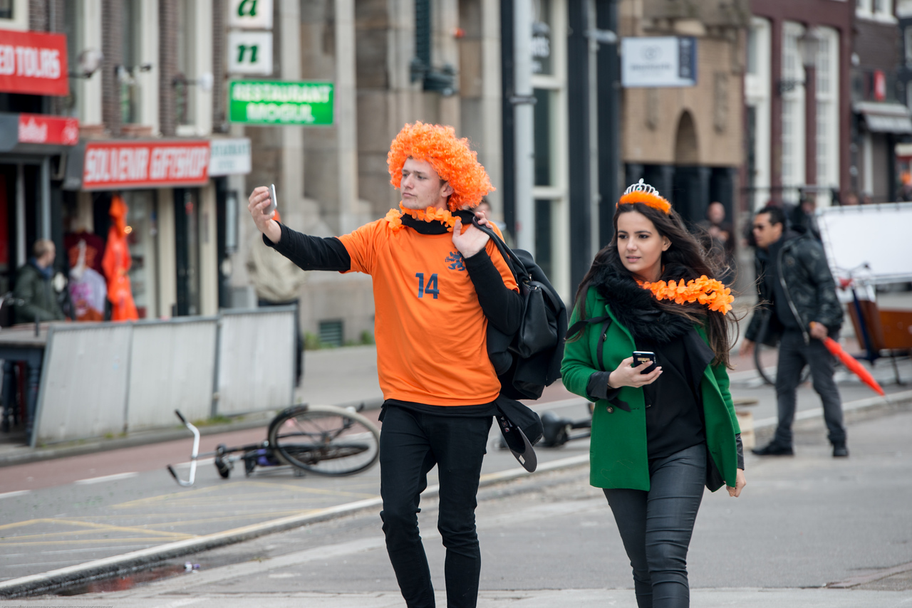 Party revelers in orange taking selfies and enjoying in the streets on King's Day (formerly Queen's Day) festivities in Amsterdam, Netherlands, Europe.