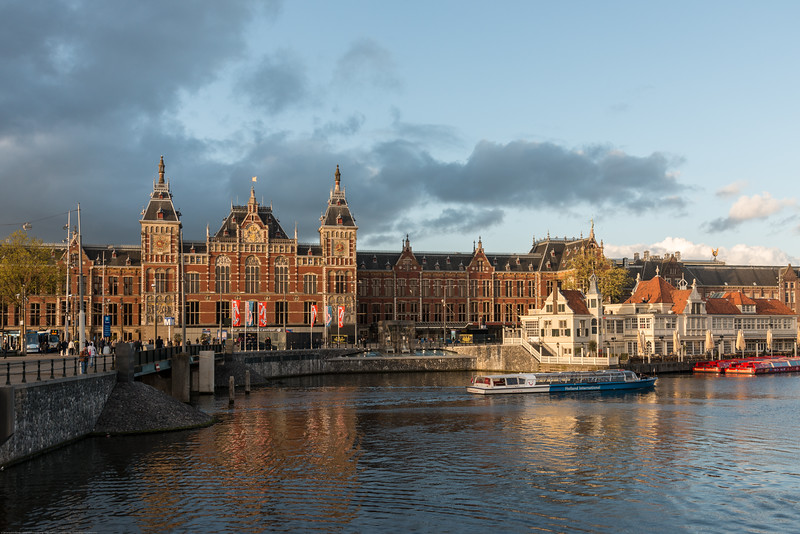 Amsterdam, Centraal Station in the background with Church of Saint Nicholas in the foreground. Amsterdam, Netherlands, Europe.