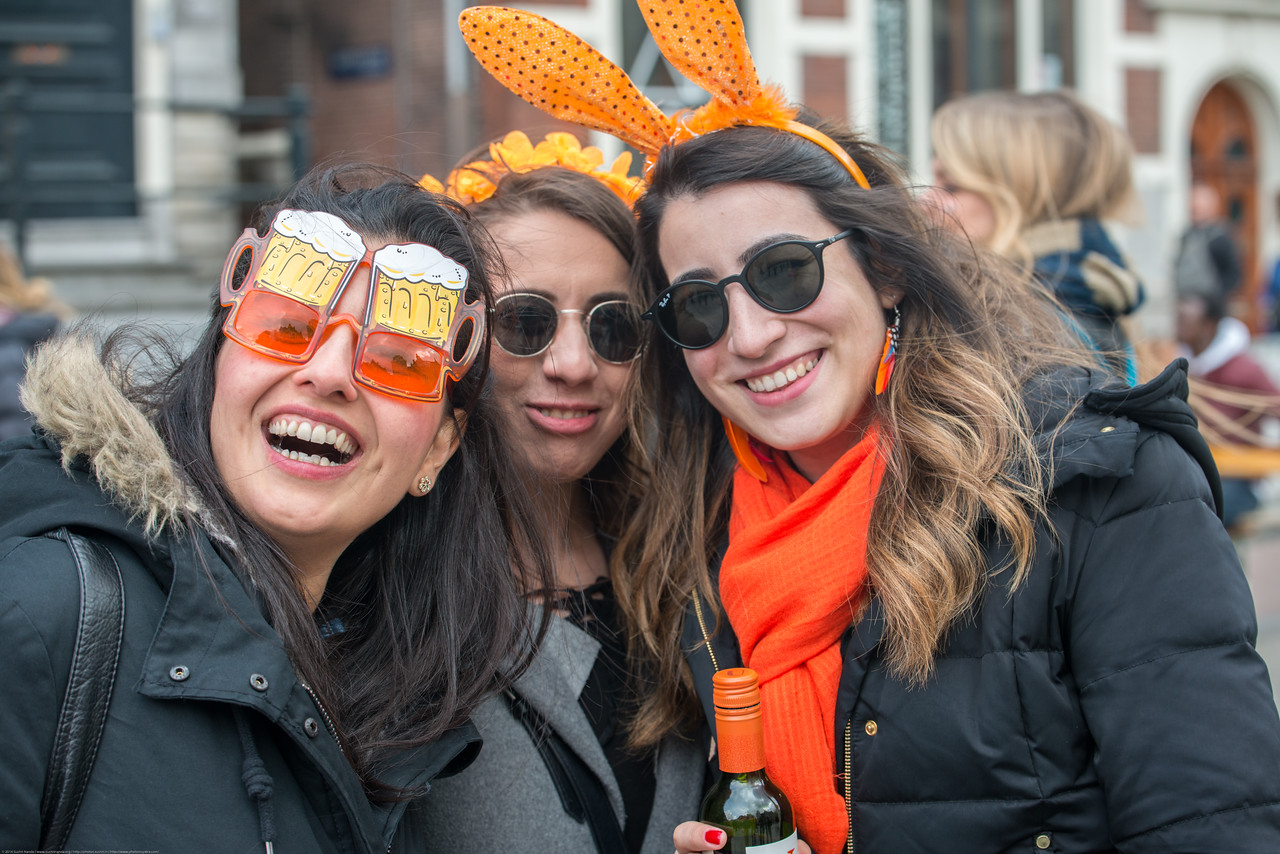 Party revelers enjoying in the streets on King's Day (formerly Queen's Day) festivities in Amsterdam, Netherlands, Europe.