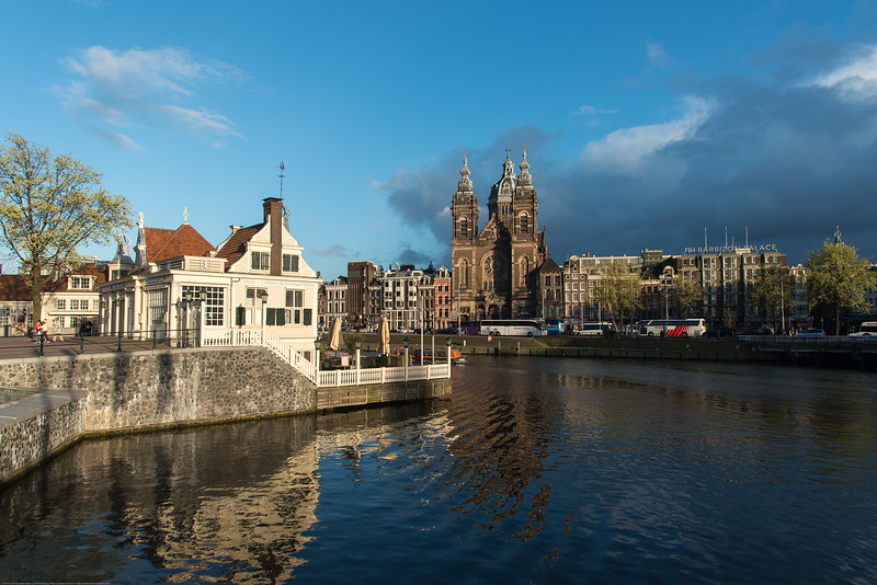 "View across the Amstel river which runs through the city of Amsterdam. The river's name is derived from Aeme-stelle, old Dutch for ""water-area"", namely, an area abounding with water. Amsterdam, the Netherlands, Europe."