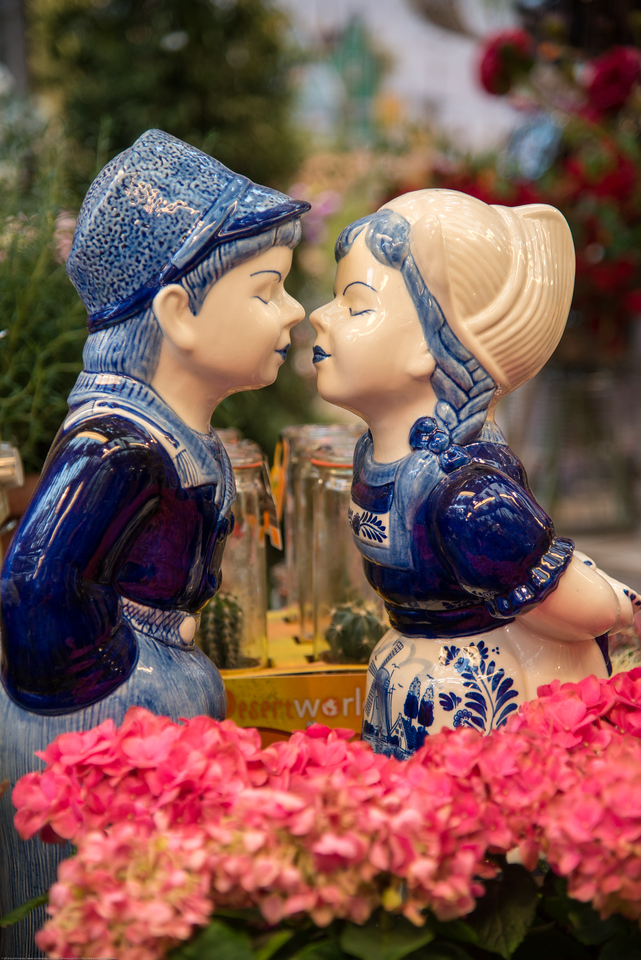 Very cute porcelain statue of a kissing boy and girl at the flower shop at Stins Flower Market, Singel, Amsterdam, Netherlands, Europe. This is the only floating flower market in the world, and one of the most fragrant places.