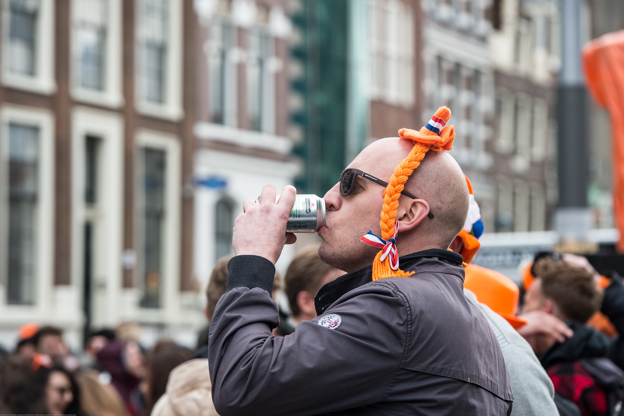 Party revelers having beer in the streets on King's Day (formerly Queen's Day) festivities in Amsterdam, Netherlands, Europe.