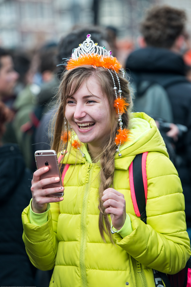 Party revelers in orange taking pictures, partying and enjoying on the streets on King's Day (formerly Queen's Day) celebrations in Amsterdam, Netherlands, Europe.