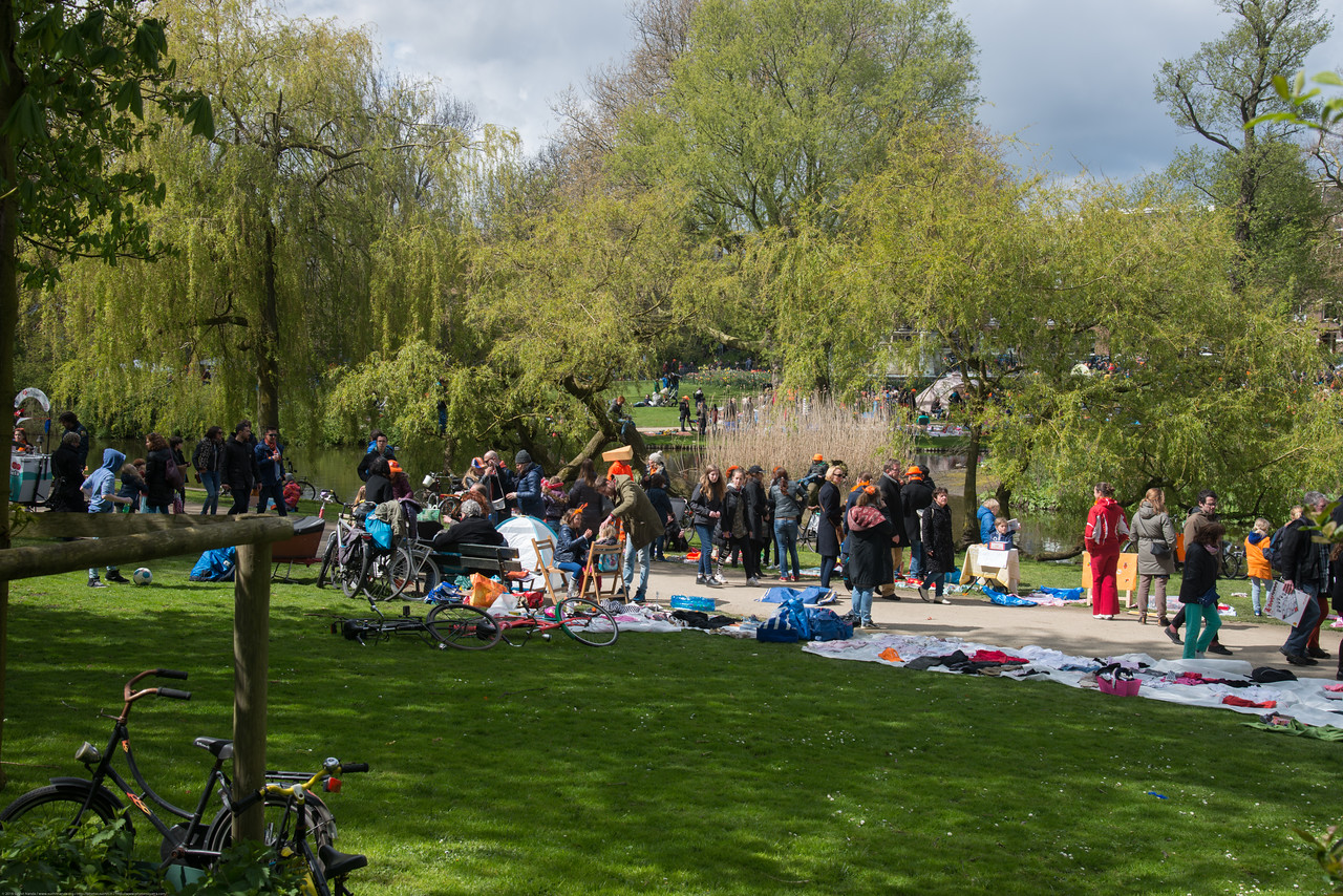 "King's Day (formerly Queen's Day) in Amsterdam at the Sarphatipark.<br /> <br /> King's Day 2016 - Koningsdag 2016 is the Dutch national holiday held on Wednesday 27 April 2016. Following the abdication of Queen Beatrix in 2013 and the inauguration of King Willem-Alexander, Queen's Day (30 April, the birthday of former Queen Juliana) has become King's Day (27 April, birthday of Willem-Alexander). One of the main highlights of King's Day is the citywide free market (vrijmarkt). This is where people set up stalls and sell clothes, food, drinks and just about anything else - from plants, old electronics, vintage items, bric-a-brac and a load of old tat. Prices are negotiable which is all part of the fun. Many Amsterdam residents set up shop directly outside their own houses - days before they mark their territory with tape (""bezet"" meaning ""occupied""). There are also professional traders and opportunists who take advantage of the tax-free trading."