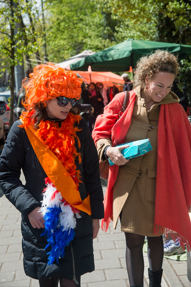"Everyone dressed in the predominant orange colour on King's Day (formerly Queen's Day) in Amsterdam.<br /> <br /> King's Day 2016 - Koningsdag 2016 is the Dutch national holiday held on Wednesday 27 April 2016. Following the abdication of Queen Beatrix in 2013 and the inauguration of King Willem-Alexander, Queen's Day (30 April, the birthday of former Queen Juliana) has become King's Day (27 April, birthday of Willem-Alexander). One of the main highlights of King's Day is the citywide free market (vrijmarkt). This is where people set up stalls and sell clothes, food, drinks and just about anything else - from plants, old electronics, vintage items, bric-a-brac and a load of old tat. Prices are negotiable which is all part of the fun. Many Amsterdam residents set up shop directly outside their own houses - days before they mark their territory with tape (""bezet"" meaning ""occupied""). There are also professional traders and opportunists who take advantage of the tax-free trading."