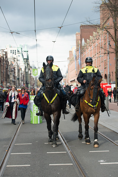 The Mayor and spouse walking down the street with police escort on the streets on King's Day (formerly Queen's Day) festivities in Amsterdam, Netherlands, Europe.