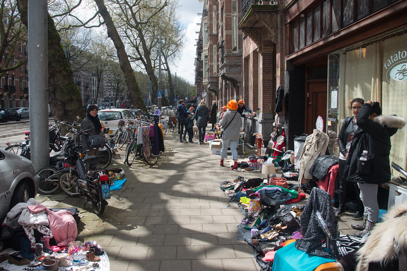 "Out no the streets on King's Day (formerly Queen's Day) in Amsterdam.<br /> <br /> King's Day 2016 - Koningsdag 2016 is the Dutch national holiday held on Wednesday 27 April 2016. Following the abdication of Queen Beatrix in 2013 and the inauguration of King Willem-Alexander, Queen's Day (30 April, the birthday of former Queen Juliana) has become King's Day (27 April, birthday of Willem-Alexander). One of the main highlights of King's Day is the citywide free market (vrijmarkt). This is where people set up stalls and sell clothes, food, drinks and just about anything else - from plants, old electronics, vintage items, bric-a-brac and a load of old tat. Prices are negotiable which is all part of the fun. Many Amsterdam residents set up shop directly outside their own houses - days before they mark their territory with tape (""bezet"" meaning ""occupied""). There are also professional traders and opportunists who take advantage of the tax-free trading"