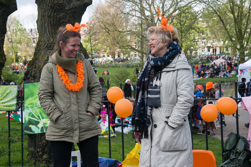 "King's Day (formerly Queen's Day) celebrations in Amsterdam at Sarphatipark.<br /> <br /> King's Day 2016 - Koningsdag 2016 is the Dutch national holiday held on Wednesday 27 April 2016. Following the abdication of Queen Beatrix in 2013 and the inauguration of King Willem-Alexander, Queen's Day (30 April, the birthday of former Queen Juliana) has become King's Day (27 April, birthday of Willem-Alexander). One of the main highlights of King's Day is the citywide free market (vrijmarkt). This is where people set up stalls and sell clothes, food, drinks and just about anything else - from plants, old electronics, vintage items, bric-a-brac and a load of old tat. Prices are negotiable which is all part of the fun. Many Amsterdam residents set up shop directly outside their own houses - days before they mark their territory with tape (""bezet"" meaning ""occupied""). There are also professional traders and opportunists who take advantage of the tax-free trading."