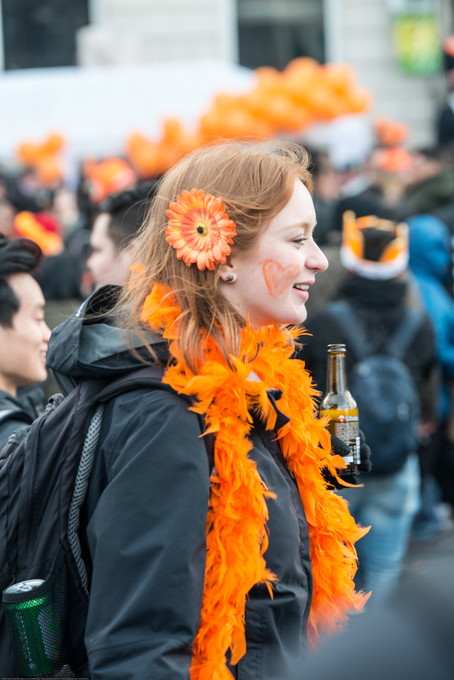Party revelers in orange drinking, smoking, partying and just enjoying on the streets on King's Day (formerly Queen's Day) celebrations in Amsterdam, Netherlands, Europe.