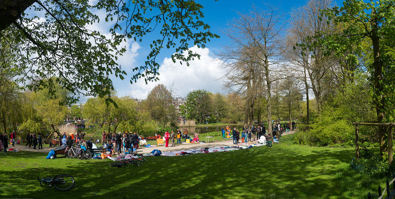 "Panoramic Sarphatipark, Amsterdam, Netherlands on King's Day (formerly Queen's Day).<br /> <br /> King's Day 2016 - Koningsdag 2016 is the Dutch national holiday held on Wednesday 27 April 2016. Following the abdication of Queen Beatrix in 2013 and the inauguration of King Willem-Alexander, Queen's Day (30 April, the birthday of former Queen Juliana) has become King's Day (27 April, birthday of Willem-Alexander). One of the main highlights of King's Day is the citywide free market (vrijmarkt). This is where people set up stalls and sell clothes, food, drinks and just about anything else - from plants, old electronics, vintage items, bric-a-brac and a load of old tat. Prices are negotiable which is all part of the fun. Many Amsterdam residents set up shop directly outside their own houses - days before they mark their territory with tape (""bezet"" meaning ""occupied""). There are also professional traders and opportunists who take advantage of the tax-free trading."