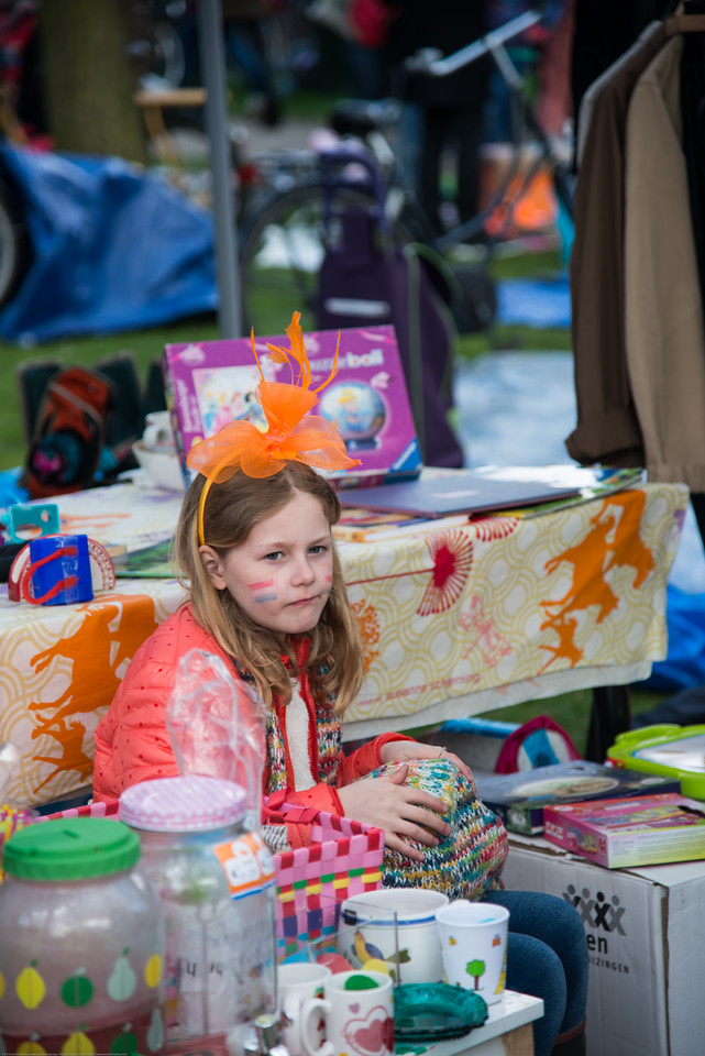 "Little girl in orange selling items on King's Day (formerly Queen's Day) in Amsterdam.<br /> <br /> King's Day 2016 - Koningsdag 2016 is the Dutch national holiday held on Wednesday 27 April 2016. Following the abdication of Queen Beatrix in 2013 and the inauguration of King Willem-Alexander, Queen's Day (30 April, the birthday of former Queen Juliana) has become King's Day (27 April, birthday of Willem-Alexander). One of the main highlights of King's Day is the citywide free market (vrijmarkt). This is where people set up stalls and sell clothes, food, drinks and just about anything else - from plants, old electronics, vintage items, bric-a-brac and a load of old tat. Prices are negotiable which is all part of the fun. Many Amsterdam residents set up shop directly outside their own houses - days before they mark their territory with tape (""bezet"" meaning ""occupied"")."