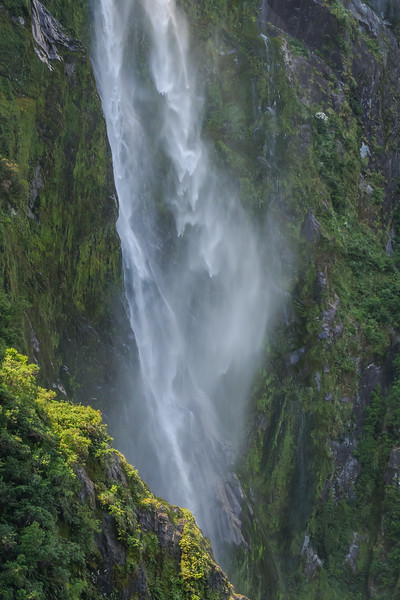 Detail of a portion of a misty waterfall falling down a moss-covered rock wall