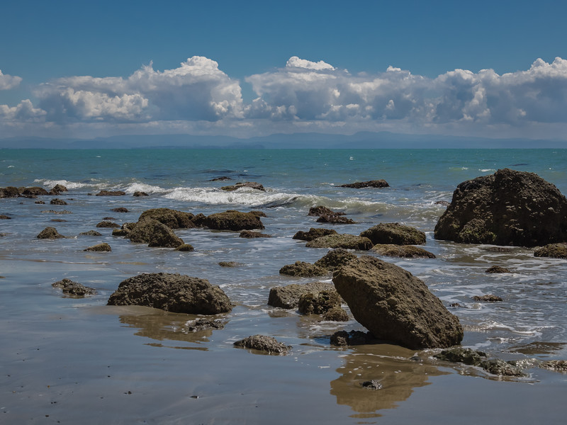 Waves swirl around rugged boulders on a sandy beach with hazy mountains visible across the water at Cape Kidnappers on Hawke's Bay in New Zealand.