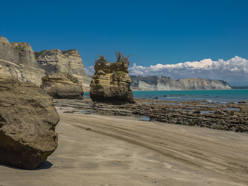 Giant boulders and sheer cliffs rise above the rocky beach at Cape Kidnappers on a beautiful sunny day at Hawke's Bay in New Zealand