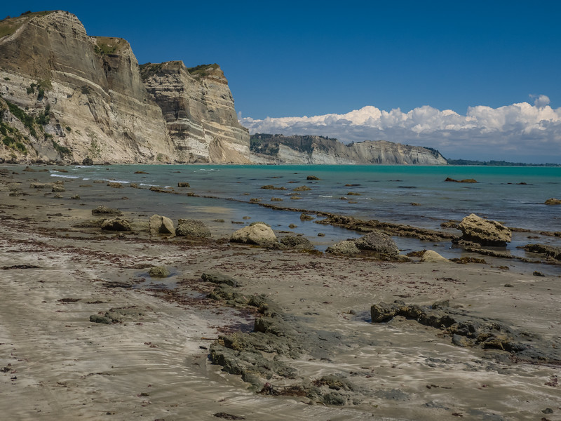 Sheer cliffs rise above the sea along the rocky shore of Cape Kidnappers on a sunny day with dramatic clouds on the horizon at Hawke's Bay in New Zealand