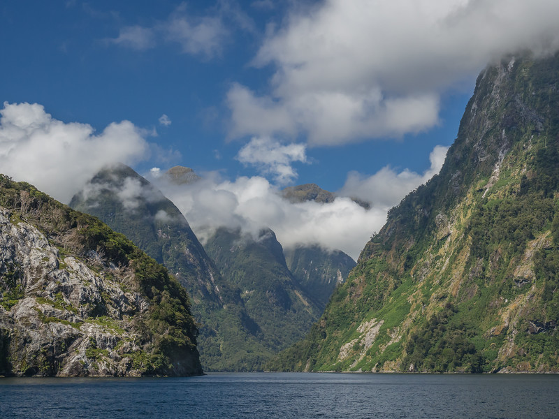 Clouds hang just below the tops of steep mountains that rise out of the fjord's waters in New Zealand