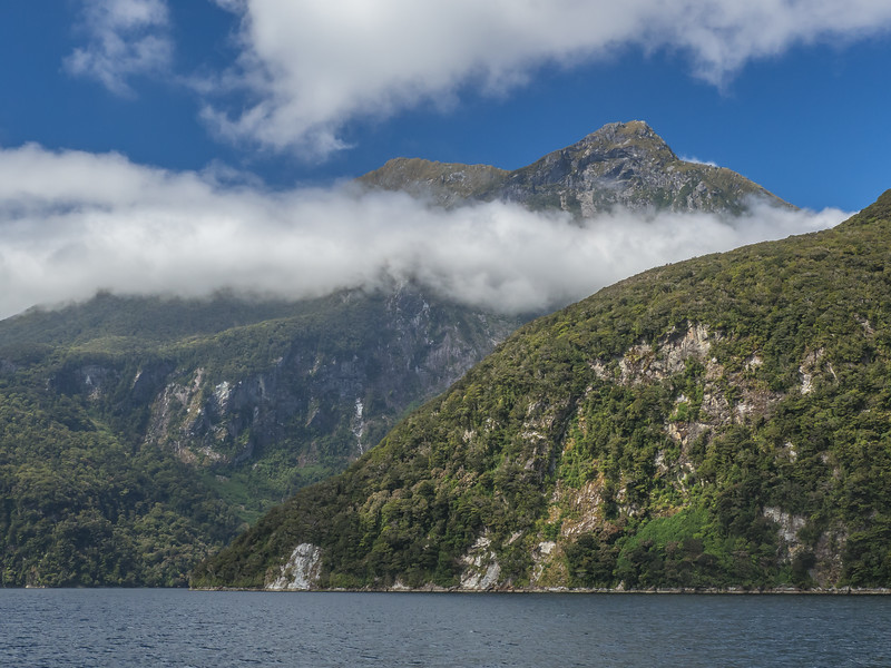 A break in the clouds reveals the rugged peaks of rocky mountainsides rising right from the water on a cruise through New Zealand's Doubtful Sound