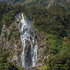 A torrent of water falls down a rocky mountainside to the sea in New Zealand