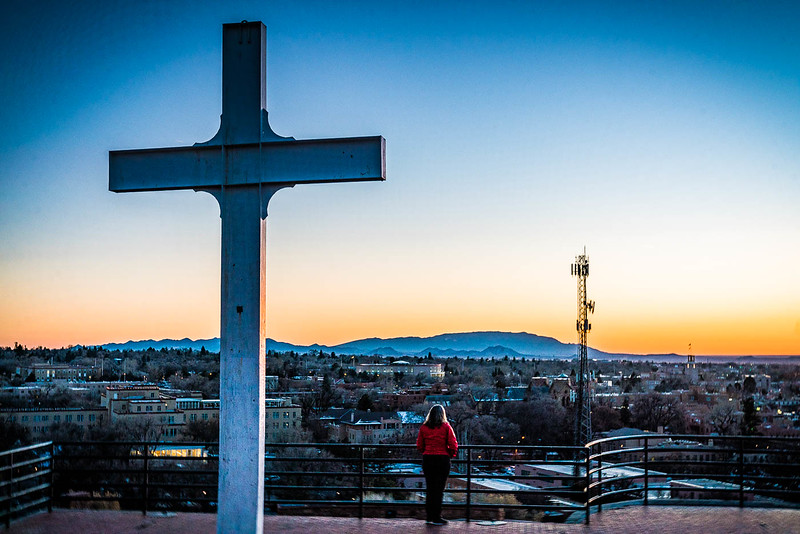 Santa Fe, New Mexico cityscape. Cross on top of Martyr's Hill in foreground, mountains in background.