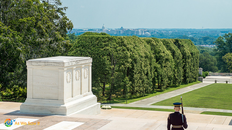 Foreground: Soldier guards Tomb of the Unknown Soldier. View of Virginia and Washington DC in background.