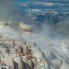 Steaming terraces below snow-capped mountains