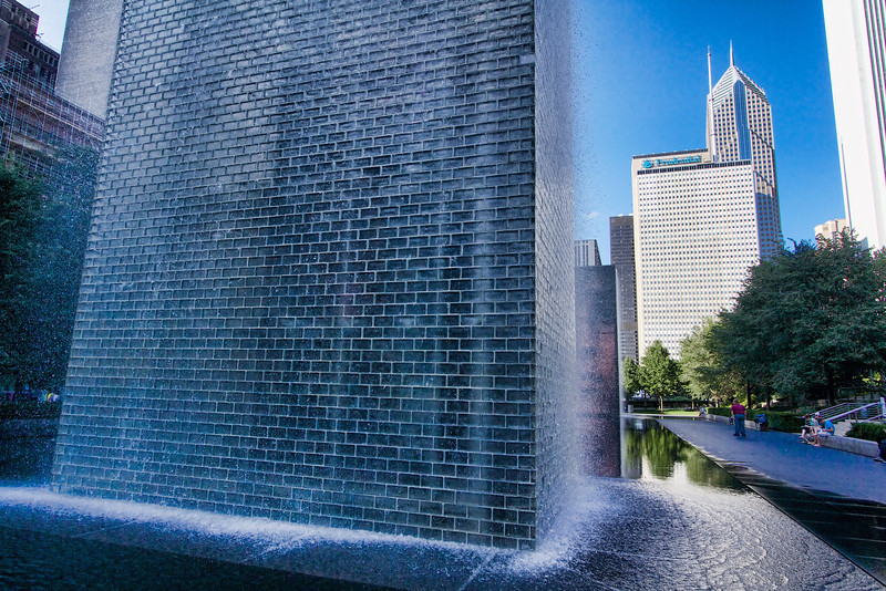 Crown Fountain - The fountain is composed of a black granite reflecting pool placed between a pair of transparent glass brick towers. The towers are 50 feet (15 m) tall, and use light-emitting diodes behind the bricks to display digital videos on their inward faces.