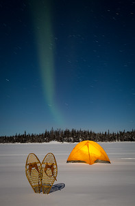 Aurora Borealis above tent and snow shoes, Yellowknife.