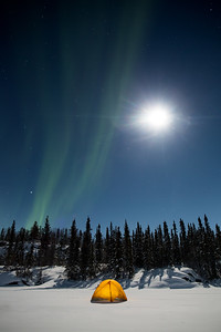 Aurora Borealis and full moon above tent, Yellowknife.