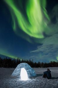 Person watching Aurora Borealis next to igloo, Yellowknife